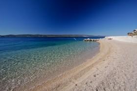 Jemné oblázky na pláži s pozvolným vstupem do moře