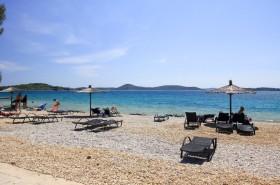 Oblázková pláž s lehátky