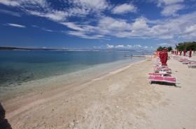 Další úsek placené pláže s lehátky a slunečníky