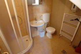 Koupelna se sprchou pro odcházející hosty