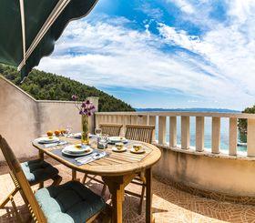 Prostorná terasa s posezením a výhledem na moře