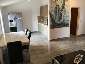 Pohled na kuchyňský stůl, kout a malbu na steně